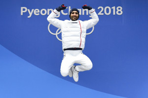 France's gold medallist Martin Fourcade jumps on the podium during the medal ceremony for the biathlon men's 15km Mass Start at the Pyeongchang Medals Plaza during the Pyeongchang 2018 Winter Olympic Games in Pyeongchang on February 19, 2018. / AFP PHOTO / Kirill KUDRYAVTSEV